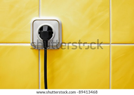 Wall outlet with a electric plug in a bathroom - stock photo