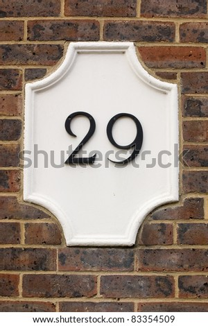 Wall plaque showing number twenty nine, 29. Outside wall of a house. - stock photo