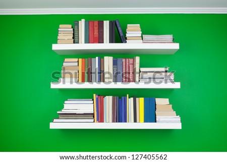 Wall shelves on green wall - stock photo