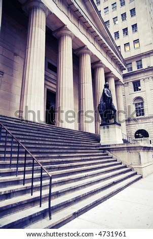 Wall St Buildings in famous downtown, NYC.  Image has a blue tone and the contrast has been increased to accentuate the pillars and columns. - stock photo
