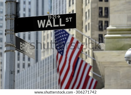 Wall street sign with focus on sign, blurred American flag background - stock photo
