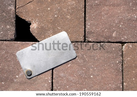 Wall with Metal Tag / Gray metal label with bolt on a old brown wall - stock photo