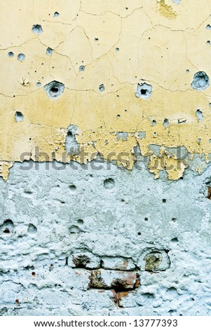 Wall with numerous bullet holes - stock photo