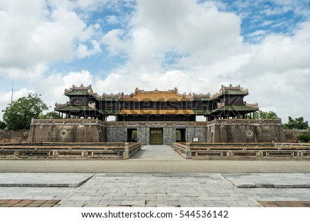 Walled fortress entrance to Hue Imperial City, Vietnam. Symmetrical frontal view with cobble stone ground and cloudy blue sky.