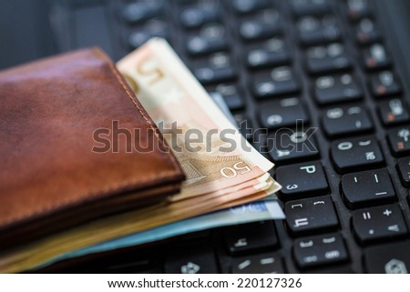 Wallet and  money on keyboard. Online banking. - stock photo
