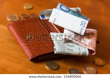 Wallet and some money scattered on a wooden table - stock photo