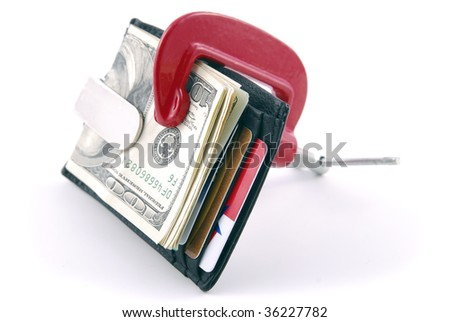 Wallet with cash and credit cards squeezed in a clamp. - stock photo