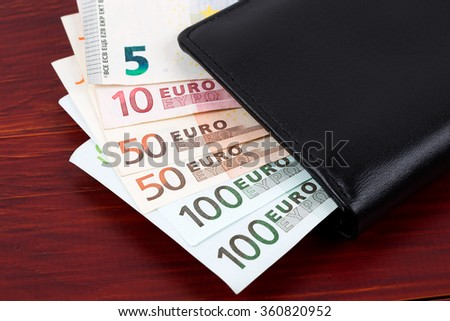 Wallet with European money on a wooden background  - stock photo
