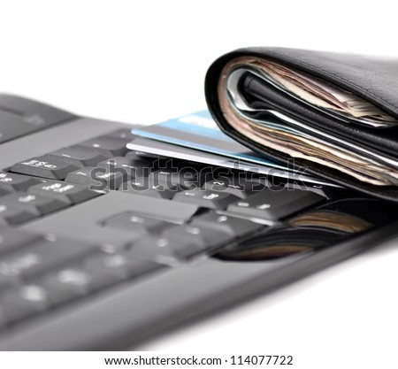 Wallet with money and bank cards on computer keyboard