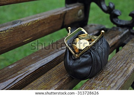 Wallet with money found on a park bench. A purse full of coins. - stock photo