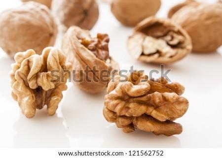 walnut and a cracked walnut on white background - stock photo