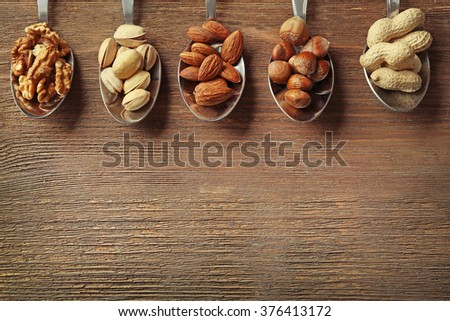 Walnut kernel, pistachios, almonds, hazelnuts and peanuts in the spoons on the wooden table - stock photo