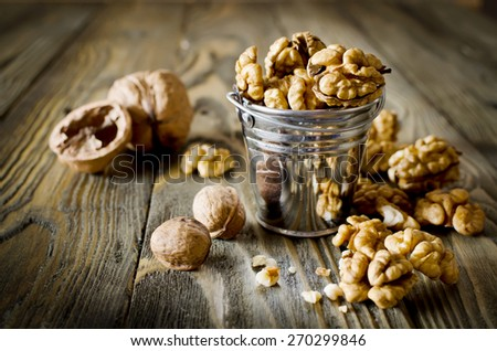 Walnut kernels and whole walnuts on wooden table. Selective Focus - stock photo