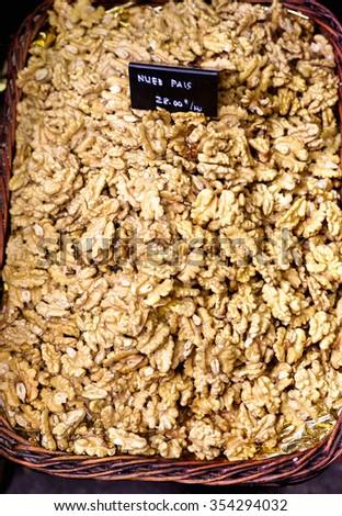 Walnut kernels in wicker basket - stock photo