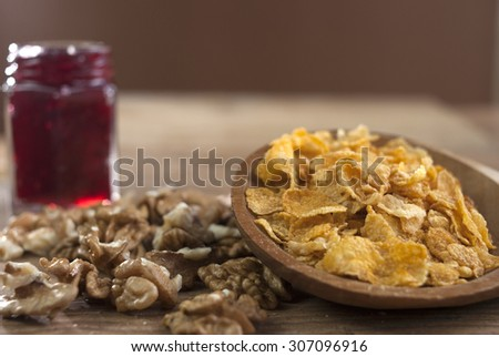 Walnuts and cornflakes on wooden spoon with jam. - stock photo