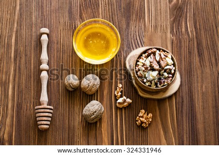 Walnuts and honey on wooden background - stock photo