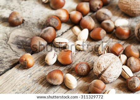 Walnuts, hazelnuts and pistachios on a wooden table, toned image, selective focus