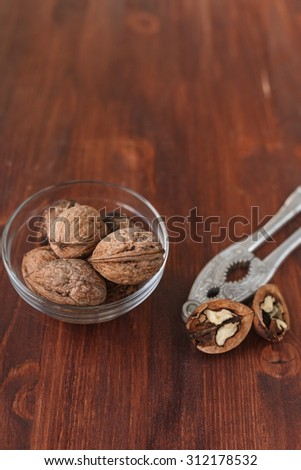 walnuts in a glass cup on a brown wooden table