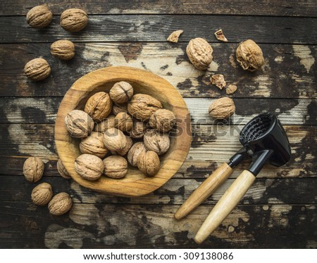 walnuts in a wooden bowl on a wooden rustic background with tongs for cracking nuts,top view - stock photo