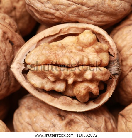 Walnuts in shells, one upon the other, one nut is open - stock photo