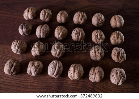 walnuts on a dark background, conceptual photography, walnuts lie in a row in a heap, an extra player, an interesting idea - stock photo
