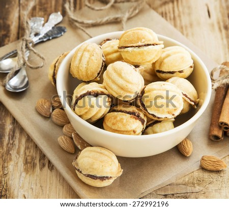 Walnuts Shape Cookies with Chocolate Filling, Sweet Homemade Cookies with Almonds and Cinnamon Sticks - stock photo