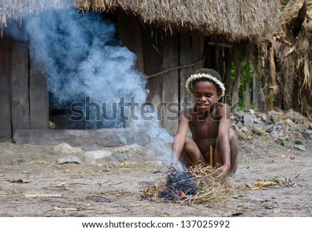 WAMENA, PAPUA, INDONESIA - NOV, 14: Papuan boy from Dani tribe, making fire on November, 14, 2008 near Wamena, Papua, Indonesia. - stock photo