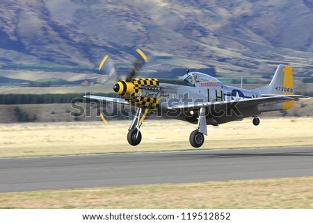 """WANAKA-MARCH 03: P-51D Mustang aircraft lands on the runway during the royal New Zealand air force 75th anniversary """"Warbirds Over Wanaka"""" airshow on March 03, 2012 in Wanaka New Zealand - stock photo"""