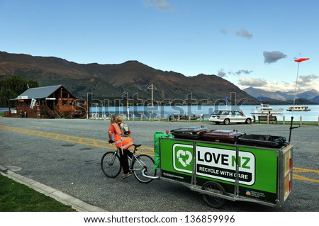WANAKA,NZ - MAR 03:Recycling bin pulled by a biker at Lake Wanaka on March 02 2009.It's New Zealand's fourth largest lake and estimated to be more than 300 m (980 ft) deep. - stock photo