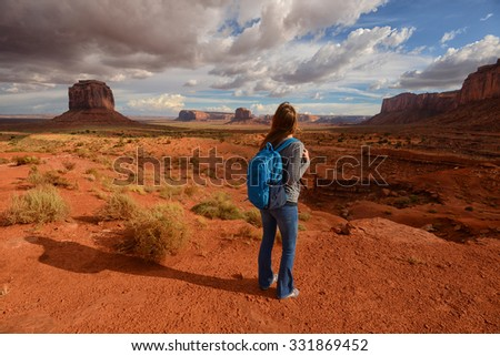 Wanderlust concept with woman traveling with backpack to the Monument Valley desert - stock photo