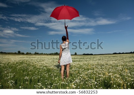 Want to fly. Woman with red umbrella above the head standing on meadow - stock photo