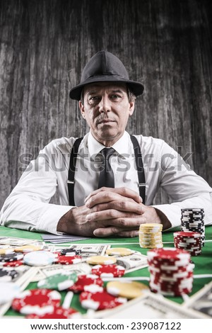 Want to play? Serious senior man in shirt and suspenders sitting at the poker table and looking at camera with cards  with money and  gambling chips laying all around him - stock photo