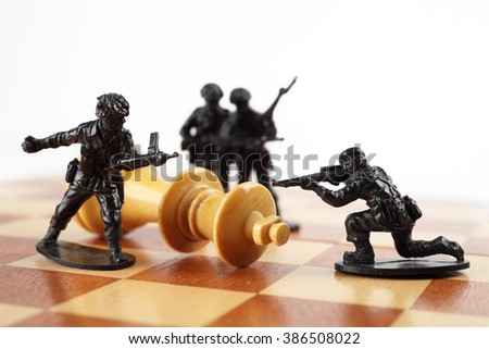 War concept. Toy soldiers kill chess King. Death of king. - stock photo