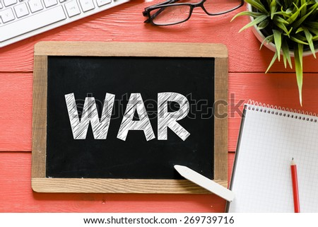 War word Handwritten on blackboard. War word Handwritten with chalk on blackboard, keyboard,notebook,glasses and green plant on wooden background - stock photo