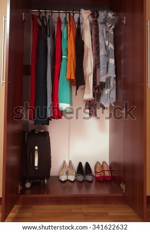 wardrobe with hanged clothes and shoes closeup