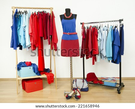 Wardrobe with red and blue clothes arranged on hangers. Dressing closet with clothes, shoes and accessories and an outfit on a mannequin.   - stock photo
