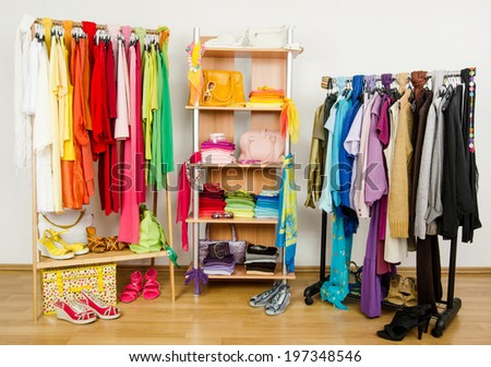 Wardrobe with summer clothes nicely arranged. Dressing closet with color coordinated  clothes and accessories on hangers and a shelf. - stock photo