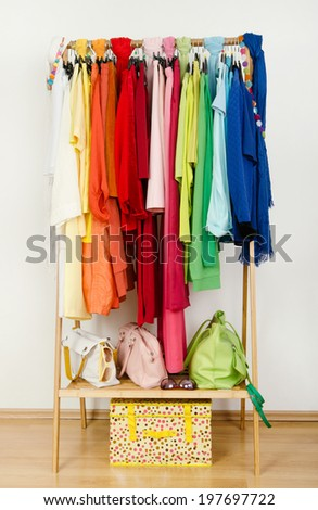 Wardrobe with summer clothes nicely arranged. Dressing closet with color coordinated clothes on hangers, bags and accessories. - stock photo