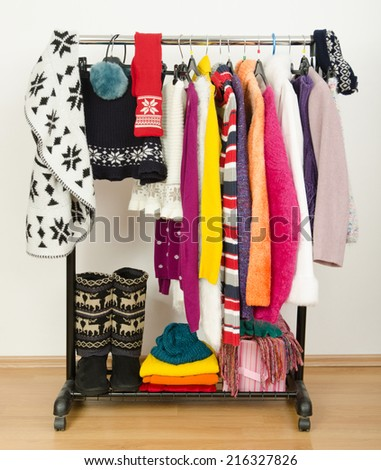 Wardrobe with winter clothes nicely arranged. Dressing closet with colorful clothes and accessories on hangers. - stock photo