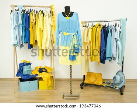Wardrobe with yellow and blue clothes arranged on hangers and an outfit on a mannequin.  Dressing closet with color coordinated clothes and accessories. - stock photo