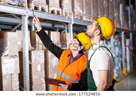 Warehouse engineer ordering to worker how to work - stock photo