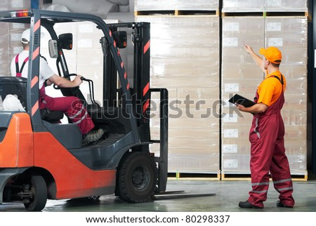 warehouse laborer team at unloading works with forklift loader - stock photo