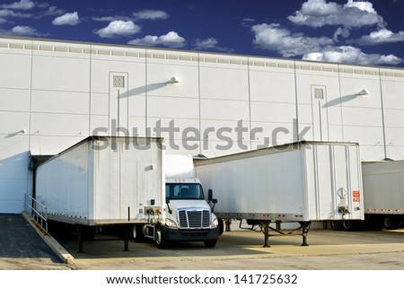 Warehouse Loading Docks - Business District. Semi Trucks and Trailers Loading. Shipping and Logistics Photography Collection. - stock photo