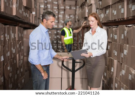 Warehouse manager and foreman working together in a large warehouse - stock photo