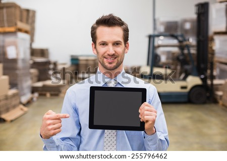Warehouse manager showing tablet pc smiling at camera in a large warehouse