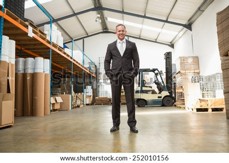 Warehouse manager standing with hands in the pocket in a large warehouse - stock photo
