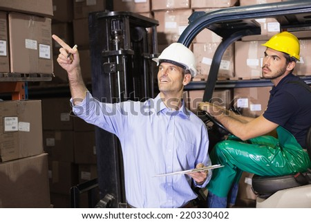 Warehouse manager talking with forklift driver in a large warehouse - stock photo