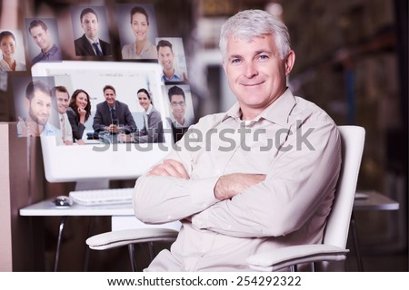 Warehouse manager using computer against portrait of a positive team sitting at a table - stock photo
