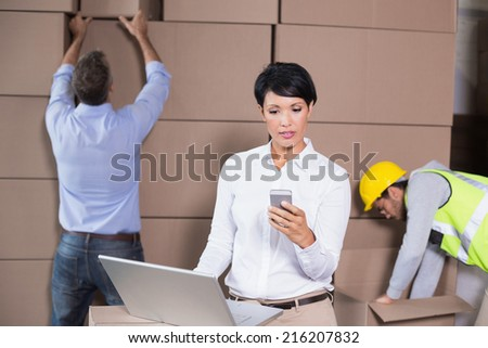 Warehouse manager using laptop and texting on phone in a large warehouse