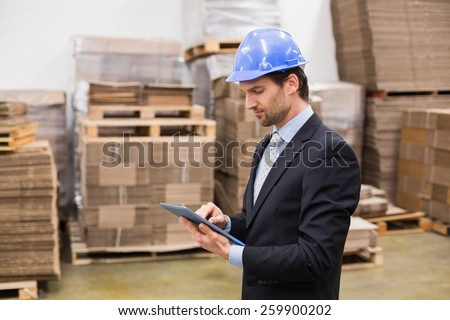 Warehouse manager wearing hard hat using tablet in a large warehouse - stock photo